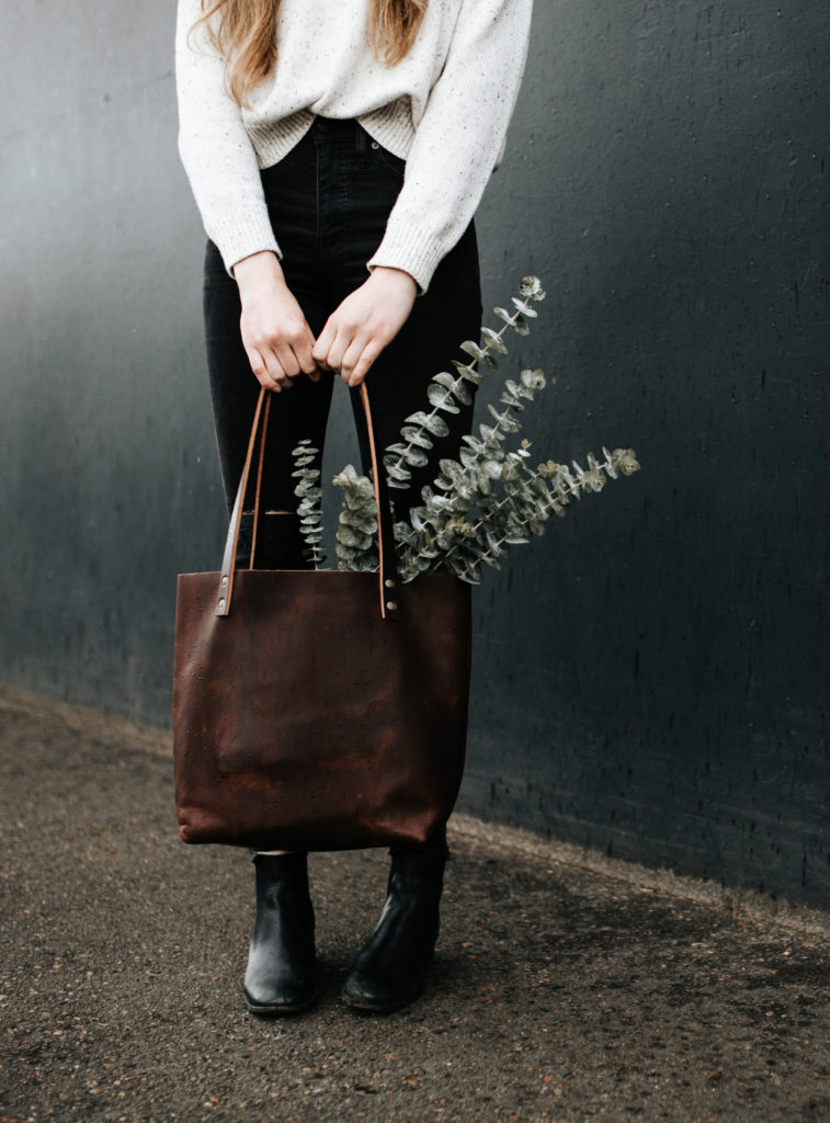 Woman carrying leather bag against a dark wall.