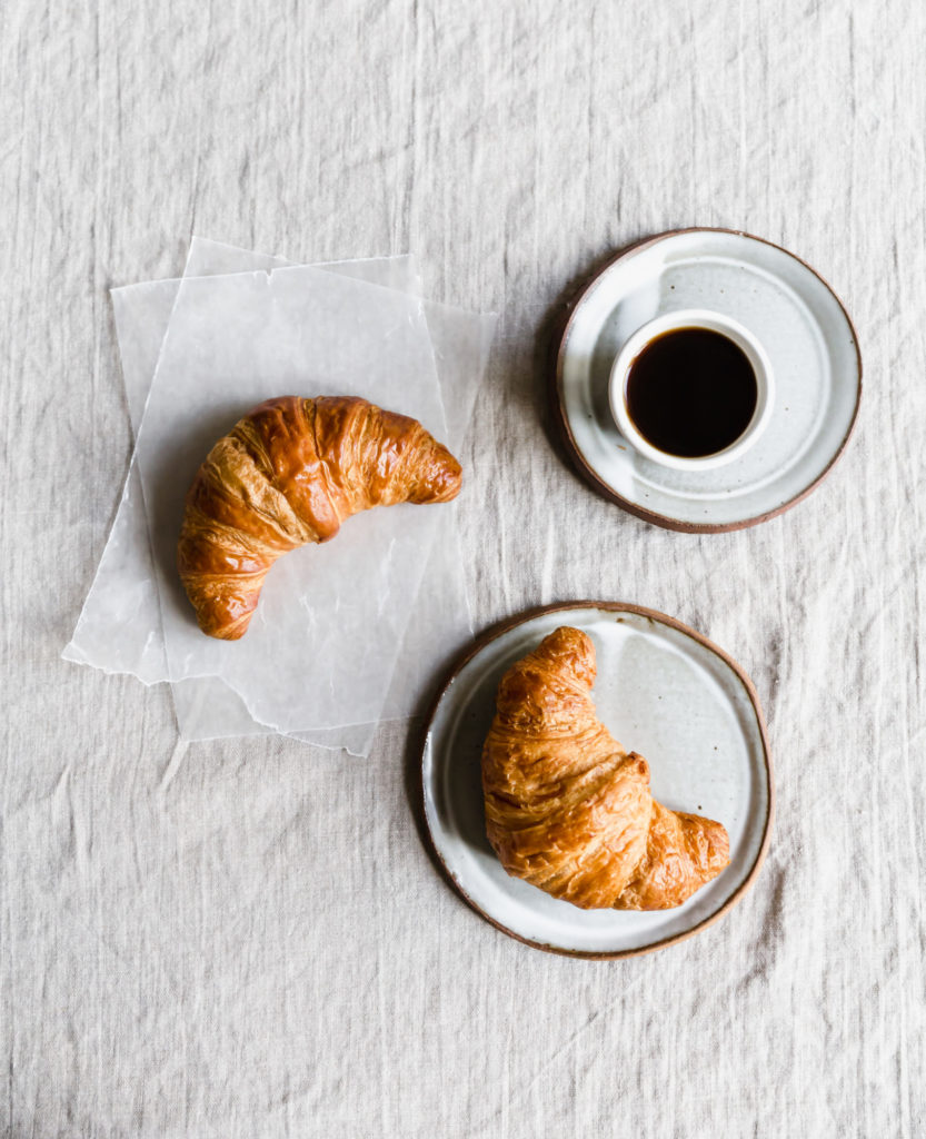 coffee and croissants on white table cloth
