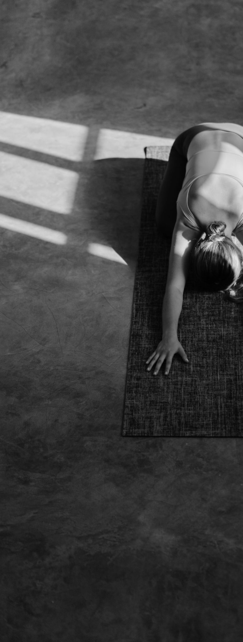 From above anonymous female doing Extended Child pose on mat on floor during yoga lesson at home