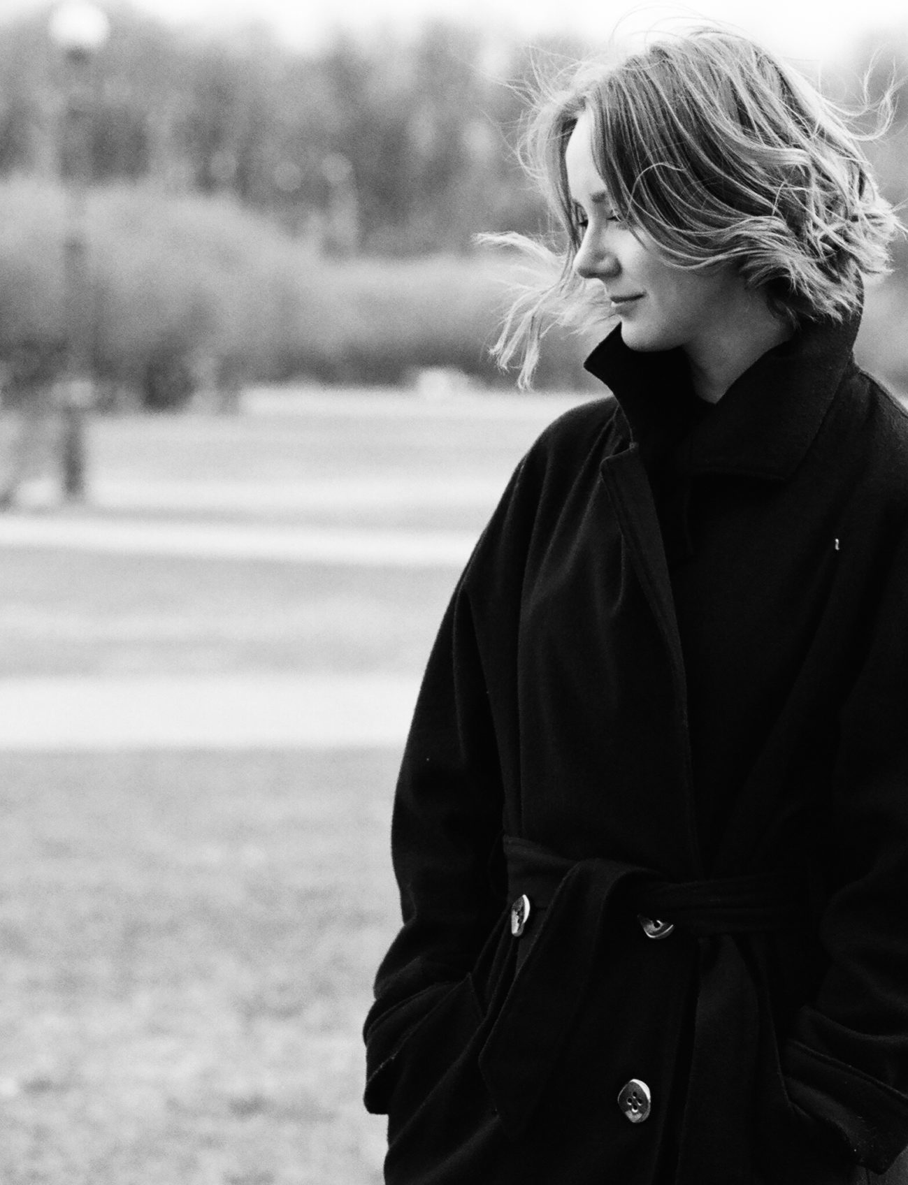 Woman in black-and-white standing outdoors wearing a coat